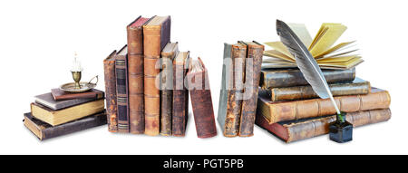 Composition of old books, candle in candlestick and feather in inkpot, isolated on black background - Stock Photo