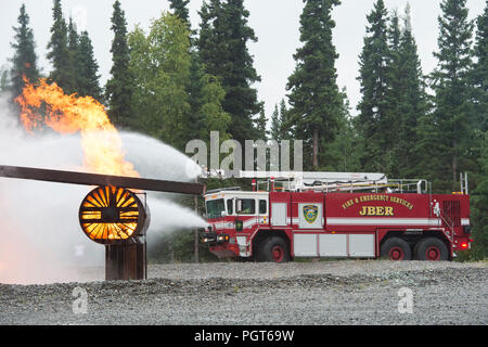 U.S. Air Force fire protection specialists assigned to the 673d Civil Engineer Squadron, spray water from their Striker aircraft rescue and firefighting vehicle while responding to a simulated aircraft fire during wartime-firefighting readiness training at Joint Base Elmendorf-Richardson, Alaska, Aug. 23, 2018. During the readiness training the Air Force firefighters donned various levels of mission oriented protective posture (MOPP) gear and practiced responding to emergency situations in a simulated toxic environment during a chemical, biological, radiological, or nuclear strike. (U.S. Air F - Stock Photo