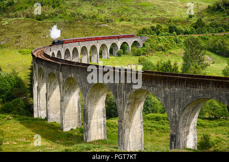 Red heritage Jacobite coal fired Steam Train used in Harry Potter films at Glenfinnan viaduct in the Scottish Highlands Scotland UK - Stock Photo