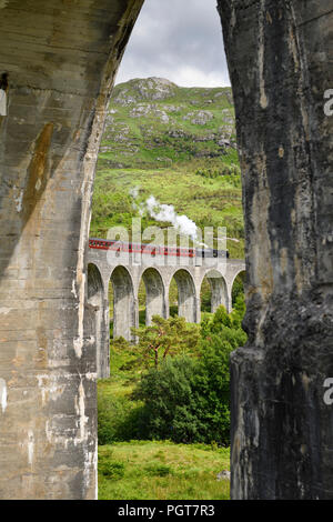 View of heritage Jacobite Steam Train through concrete columns of the Glenfinnan viaduct in the Scottish Highlands Scotland UK - Stock Photo