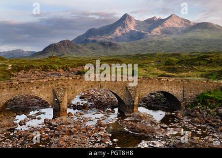 Sligachan Old Bridge over River Sligachan with Sgurr nan Gillean peak of Black Cuillin mountains with last sunset light Scottish Highlands Scotland - Stock Photo
