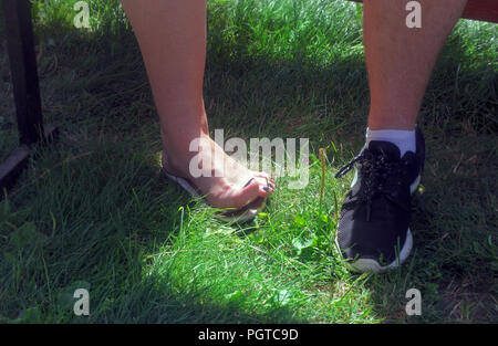 Women's and men's leg on green sunny summer grass - Stock Photo
