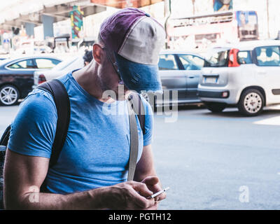 Tourist in a baseball cap and with a backpack - Stock Photo