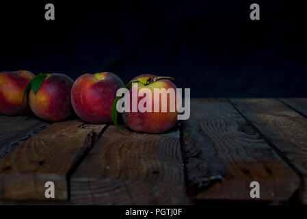 Fresh juicy peaches with leaves on dark wooden rustic table on a black background - Stock Photo
