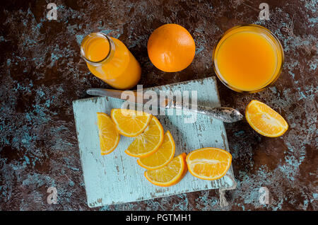 orange juice in a glass and a bottle and pieces of orange on a concrete brown-blue background copy space - Stock Photo