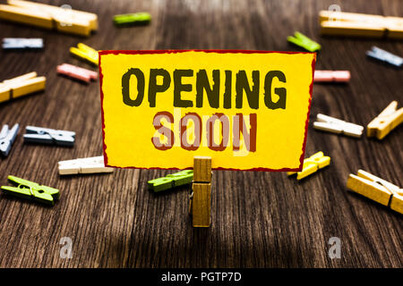 Handwriting text writing Opening Soon. Concept meaning Going to be available or accessible in public anytime shortly Clothespin holding yellow paper n - Stock Photo