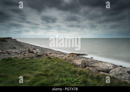 The deserted western shoreline and beach of Walney Island off the Cumbrian coast in summer with long exposure on the sea and shingle beach. - Stock Photo