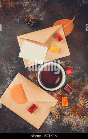 Enamel cups of tea, watercolors in cuvettes, two envelops, greetings card, autumn leaves and bumps on a rusty brown background - Stock Photo
