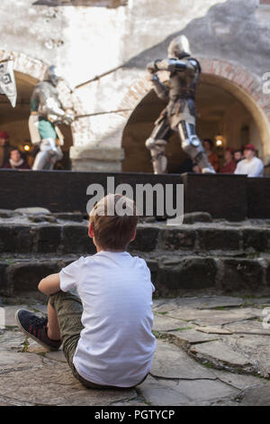 A little boy watching the battle of two knights on the castle yard at the medieval festival 'Al cospetto dei Conti di Gorizia 2018' - Stock Photo