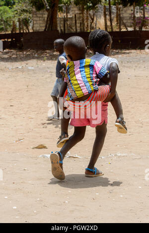 ORANGO ISLAND, GUINEA BISSAU - MAY 3, 2017: Unidentified local little girl carries her little brother on her back in the Etigoca village. People in G. - Stock Photo