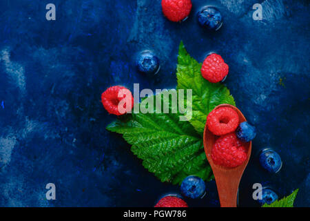 Summer berries in wooden spoons top view. Raspberry and blueberry mix on a dark blue wet background with copy space. Raw ingredients from above - Stock Photo