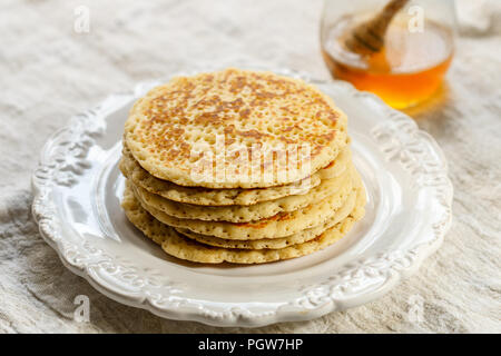 Delicious sweet American pancakes with honey on a white plate. Breakfast is gourmet. Selective focus - Stock Photo