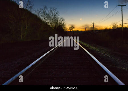 Mercury, Venus, and a waxing crescent moon line the evening sky above the setting sun and a set of railroad tracks. - Stock Photo