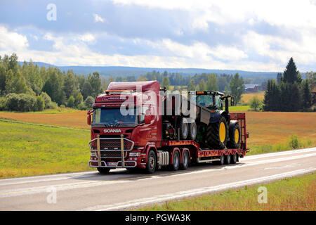 JAMSA, FINLAND - AUGUST 27, 2018: Red Scania R450 truck hauls agricultural tractor and trailer along road through Finnish rural scenery in late summer - Stock Photo