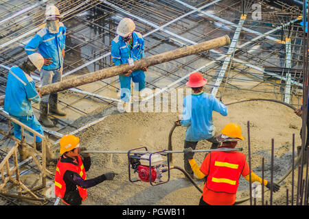 Construction workers using a concrete vibrator (gasoline engine type) at the construction site to compact the liquid concrete in reinforcement form wo - Stock Photo