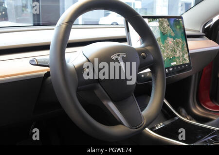 AUCKLAND - AUG 28 2018:The insignia of Tesla on the wheel of the plug-in electric car Model 3, a mid-size / compact executive luxury four-door sedan m - Stock Photo