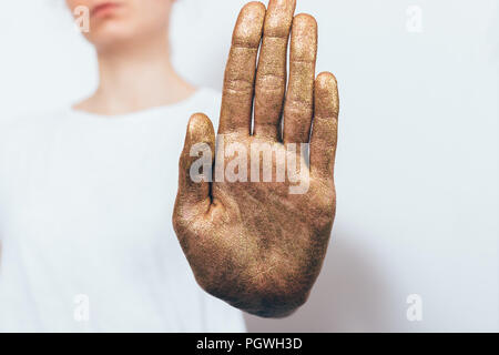 Young woman showing her palm saying no. Female standing on white background refusing proposal and making stop gesture with her hand covered with golde - Stock Photo