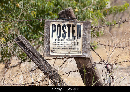 No trespassing, No hunting, No fishing, No trapping sign on fence post on rural private property - California USA - Stock Photo