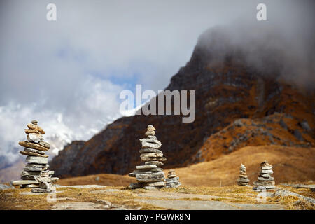 Small piles from stones on the Mardi Himal trek and cloudy peaks of Himalaya Mountains in Nepal - Stock Photo