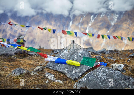 Small piles from stones and Tibetan prayer flags Lung Ta at the Mardi Himal Base Camp at cloudy peaks of Himalaya Mountains in Nepal - Stock Photo