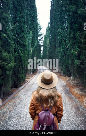 Woman in brown hat with backpack looking at cypress alley in botanical garden of Tbilisi, Georgia - Stock Photo