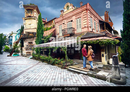 Tourist woman in brown hat and man in red shirt looking on tower of puppet museum at the street of central Tbilisi, Georgia - Stock Photo