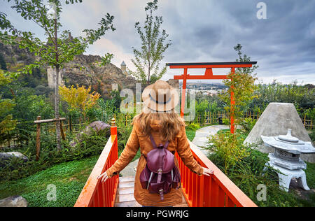 Woman in brown hat in Japanese garden and old castle Narikala at overcast cloudy sky in botanical garden of Tbilisi, Georgia - Stock Photo