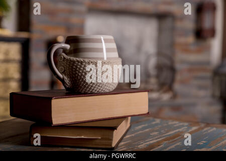 Old books and cup of coffee on wooden grunge table over fireplace background.Composition with stack of books and cup of coffee,tea,cocoa,copy space.Toned image.winter morning concept. - Stock Photo