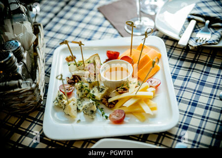 Cheese plate Assortment of various types of cheese and honey on white plate.Cheese and wine party table, perfect holiday appetizer. Different types of cheeses.raw food concept. - Stock Photo