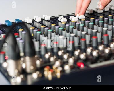 Dj adjsuting fade sliders on audio mixer close up - Stock Photo