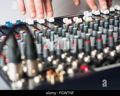 Man working on audio mixer in music studio - Stock Photo