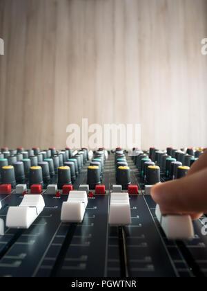 Producing music in studio on audio mixer close up - Stock Photo