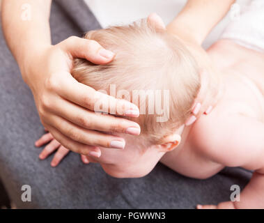 Seven month baby girl skull and neck are manipulated by osteopathic or chiropractic manual therapist - Stock Photo