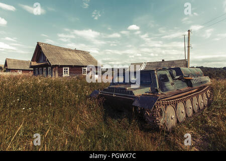 Abandoned all-terrain vehicle in the Russian hinterland. Old village houses. - Stock Photo