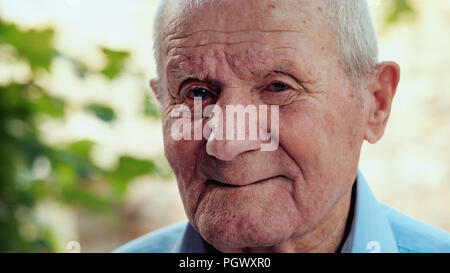 Very old man portrait with emotions. Grandfather is smiling and looking to camera. Portrait: aged, elderly, senior. Close-up of old man sitting alone outdoors. - Stock Photo