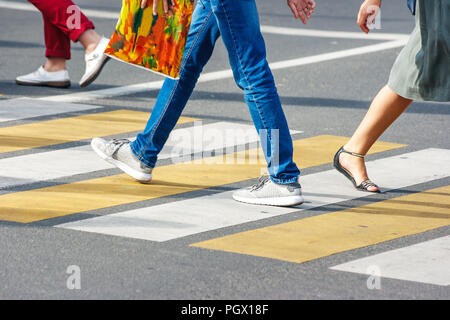 many legs of people crossing the pedestrian crossing in the busy street of the downtown on the sunny summer day - Stock Photo