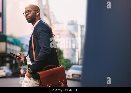 African businessman with bag walking on the street with mobile phone. Handsome businessman listening music from smart phone while walking on city stre - Stock Photo