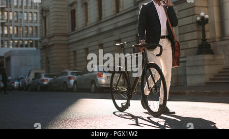 Cropped image of businessman walking on city street with a bicycle and talking on mobile phone. Man in formal wear going to work with cycle using phon - Stock Photo