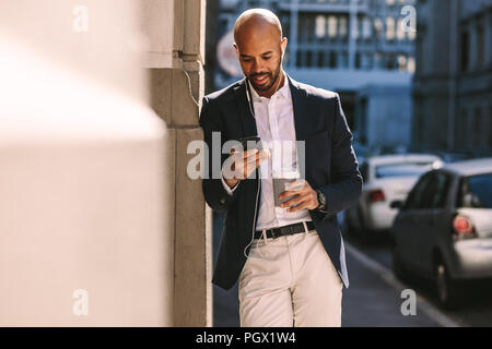 Handsome businessman leaning on a wall while standing outdoors and using smartphone. Man in suit wearing earphones looking at his mobile phone. - Stock Photo