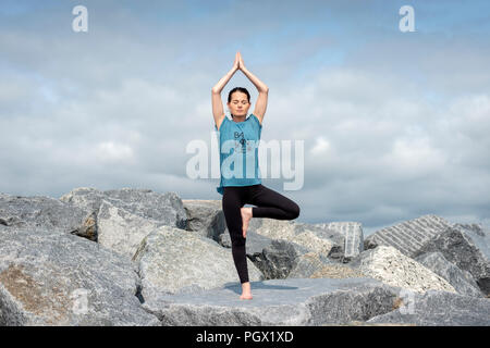 woman standing doing yoga, tree pose, wearing a tshirt with 'balance' slogan. - Stock Photo