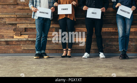 Low section of business people holding placard with their department name against wooden wall in office. - Stock Photo