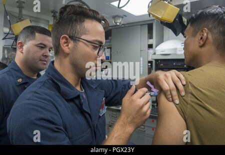 Seaman Santiago Arevalo-Mendoza administering a Japanese encephalitis vaccine to a Sailor aboard the Arleigh Burke-class guided-missile destroyer USS Benfold (DDG 65), East China Sea, August 22, 2018. Image courtesy Petty Officer 2nd Class Elesia Patten / U.S. Navy. () - Stock Photo