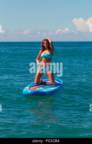 Hobby. Healthy Happy Athletic Girl In Wetsuit Paddling On Stand Up Paddle. SUP Board In Ocean. Summer Fun, Holidays Travel Vacation. Lifestyle. Recreational Water Sports. Leisure Activity - Stock Photo