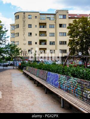 Friedrichshain-Berlin, Revaler Strasse stret view, apartment building, park, graffiti covered wooden benches - Stock Photo