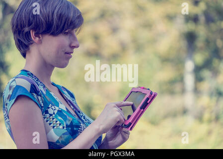 Attractive young woman standing in profile using a pink tablet outdoors navigating the touch screen with her finger against greenery with copyspace, v - Stock Photo