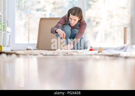 Young Woman assembling a DIY furniture at home kneeling on the floor in front of a bright glass window surrounded by materials and tools working with  - Stock Photo