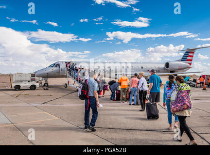 Passengers board an American Airlines American Eagle Embraer 140 aircraft from the tarmac using airstairs at the airport in Roswell New Mexico USA. - Stock Photo