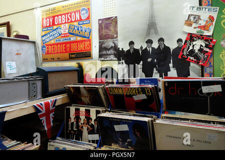Iconic posters and vinyl records on sale with Bric-à-brac on display an English Antiques centre - Stock Photo