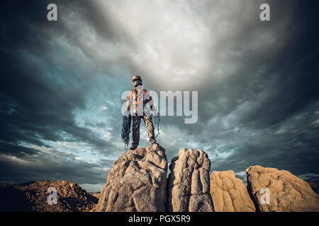 Climber on the summit of a rock spire after a successful ascent. - Stock Photo