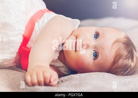 Portrait of cute adorable blonde Caucasian smiling baby child girl with blue eyes in white dress with red bow lying on bed looking up dreaming, fairy